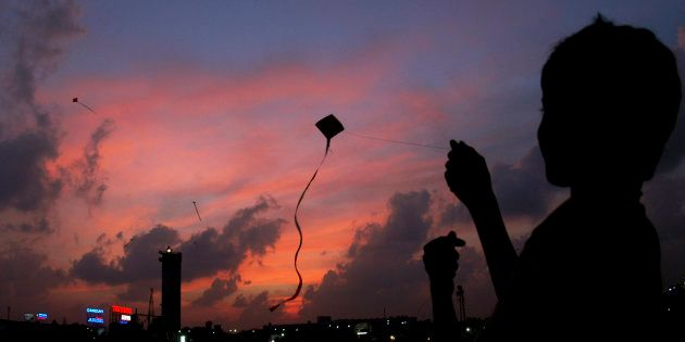 A boy flies a kite in the evening in Chennai February 2, 2007. REUTERS/Babu