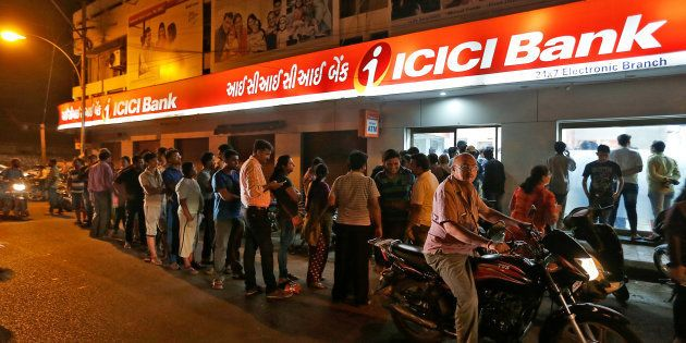 People wait to deposit and withdraw their money outside an ICICI Bank ATM in Rajkot, India, November...
