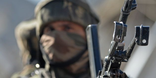 An Indian army soldier stands guard near the scene of an attack on a Indian Central Reserve Police Force...