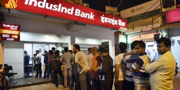People queue up outside ATMs to withdraw hundred rupee notes at sector 12 on November 8, 2016 in Noida,...