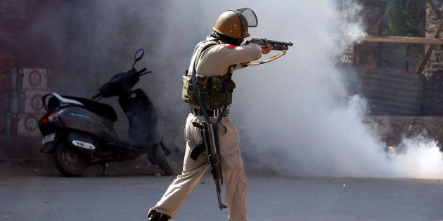 A policeman aims a tear gas gun towards demonstrators during a protest in
