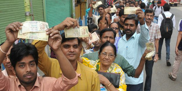 People queue up to deposit and change old currency at the State Bank of India in Salkiya, Howrah, Kolkata,...