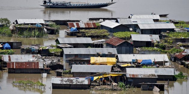 Villagers use a boat as they row past partially submerged houses at a flood-affected village in Morigaon...