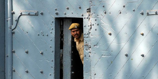 A policeman peers from inside the gate of Chanchalguda jail in
