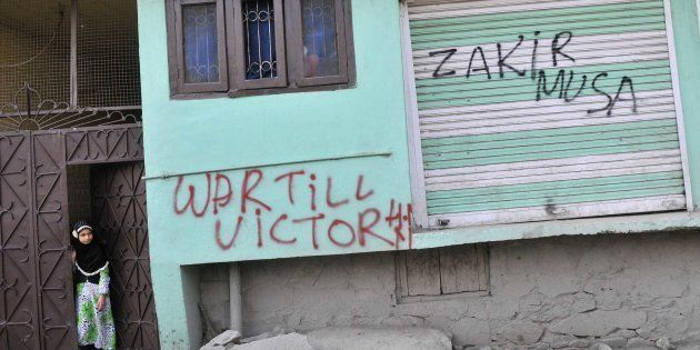SRINAGAR, INDIA - JULY 8: Kashmiri children stand next to graffiti that reads War till Victory and a...