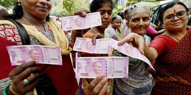 Chennai: Women show their new Rs 2000 notes after exchanging their old Rs 500 and Rs 1000 notes at a...