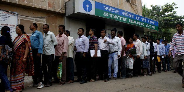 People stand in the queue to enter into the bank to withdraw money and exchange the discontinued