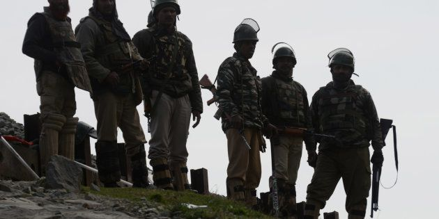 Indian paramilitary soldiers guard outside a polling station during a re-polling of a by-election for...