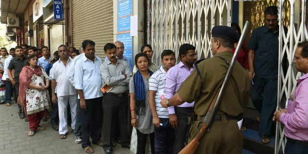 Indians queue up outside the Bank of India branch to deposit and exchange 500 and 1000 currency notes...