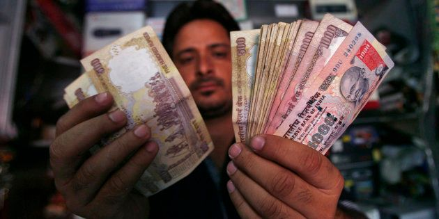 A shopkeeper poses for a picture as he counts Indian currency notes at his shop in Jammu May 16, 2012....