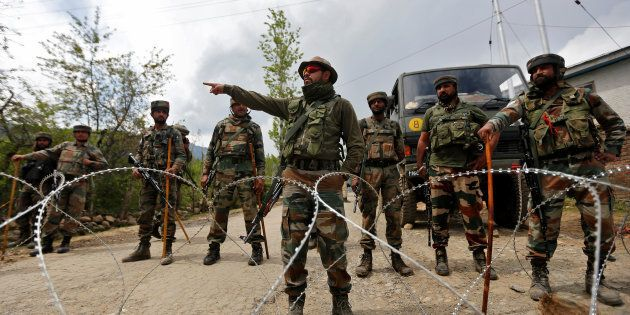 Indian army soldiers stand guard inside their army base after it was attacked by suspected separatist...