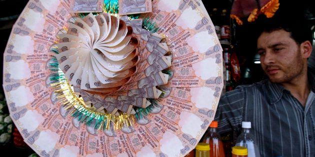 A Kashmiri shopkeeper displays a garland made of Indian currency notes at a market in Srinagar May 20,
