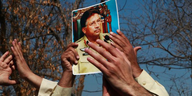 A supporter holds a picture of former Pakistani President Pervez Musharraf, during a protest with others...