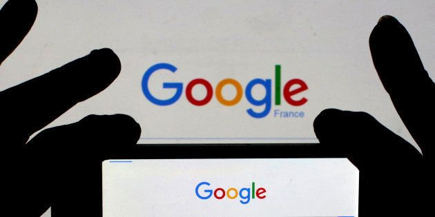 A woman holds her smart phone, which displays the Google home page, in this picture illustration taken...