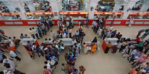 People wait in lines to deposit and withdraw money inside a post office in Lucknow, India, November 10,...