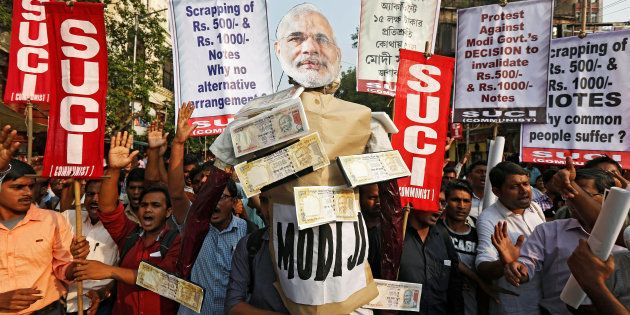 Activists of Socialist Unity Centre of India (SUCI) shout slogans as they carry an effigy of Prime Minister...