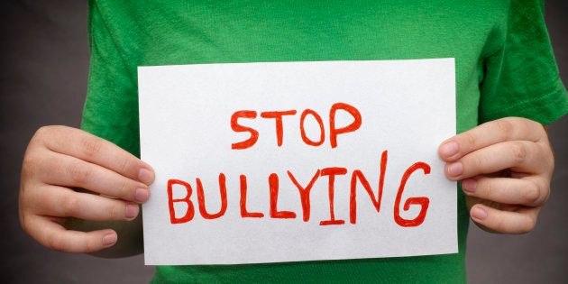 A young boy holds Stop bullying