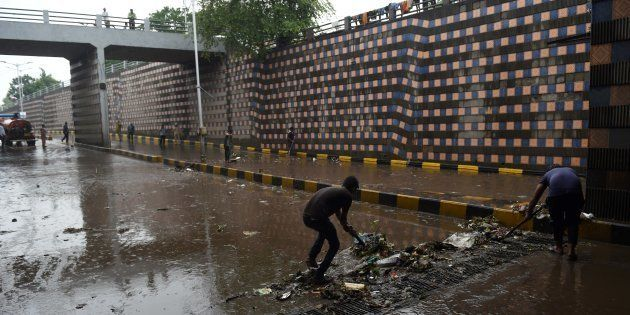 REPRESENTATIVE IMAGE: Indian workers clear blocked drains following heavy rain and flooding in Ahmedabad...