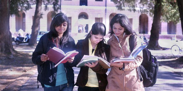 REPRESENTATIVE IMAGE of three college students discussing their notes after