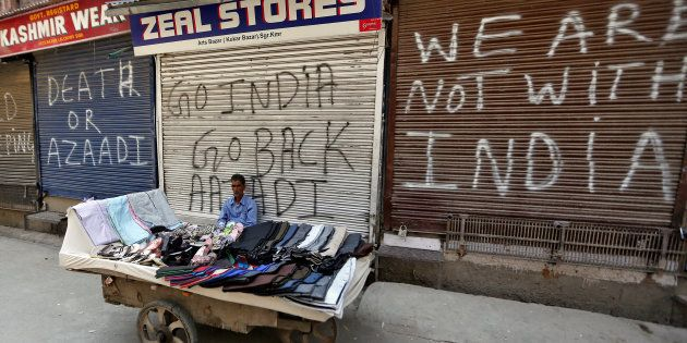 A vendor sits in front of closed shops during a strike called by Kashmiri separatists to protest the...