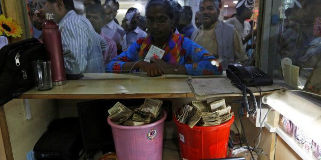 Old high denomination bank notes are seen kept in buckets at a counter as people stand in a queue to...