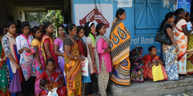 Customers in the Bhutkirhut Village on the outskirts of Siliguri form queues outside banks to deposit...