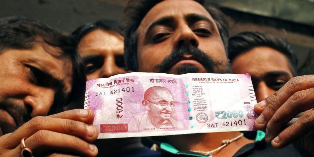 A man displays a new 2000 Indian rupee banknote after withdrawing from a bank in Jammu, November 11,...