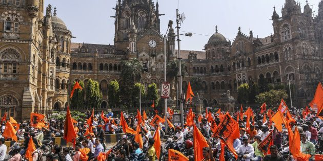 Demonstrators with saffron flags ride motorcycles past the Chhatrapati Shivaji Terminus railway station...