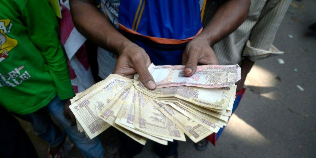 File photo of a man holding Rs. 500 and Rs. 1000 bank notes while waiting in line outside a bank to exchange