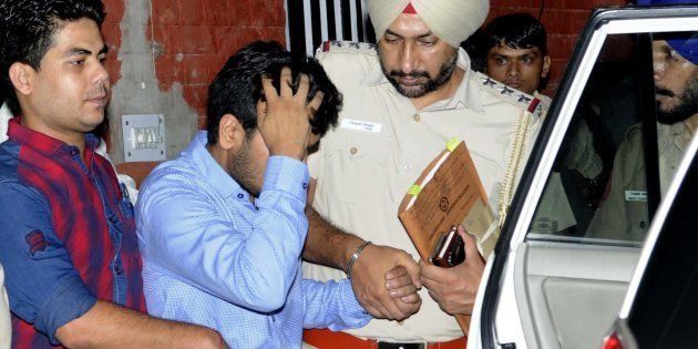 Vikas Barala (in blue shirt) being taken into Chandigarh police custody at Sector 26 Police