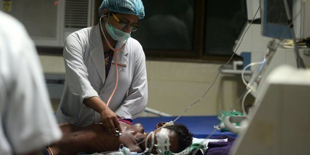 Indian medical staff attend to a child admitted in the Encephalitis ward at The Baba Raghav Das Hospital...