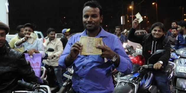 A man showing notes of ₹500 as people rushed to petrol pump to use their notes of ₹500 and ₹1,000 on...