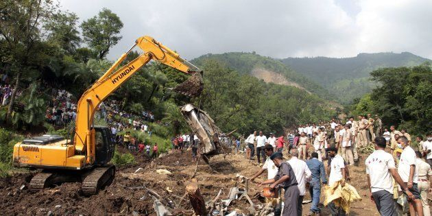 Heavy machinery removes debris as rescue personnel search for survivors and bodies of victims after a...