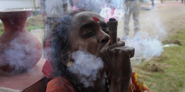 An Indian holy woman smokes marijuana on the eve of the traditional Kharchi Puja festival at