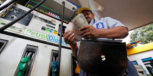 File photo of an employee counting Indian currency at a fuel station in