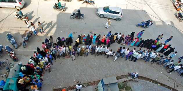 People queue to deposit or exchange their old high denomination banknotes outside a