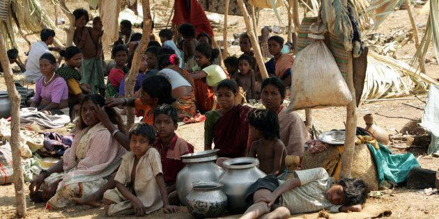 A group tribals sit in open at a camp in Dornapal in the central state of