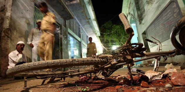 [FILE PHOTO] People walk past a damaged bicycle lying at a blast site inside a mosque in Malegaon on...