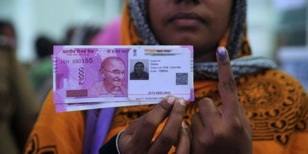 Woman poses with new ₹2,000 notes, her Aadhaar ID card and a finger inked with indelible ink after exchanging...