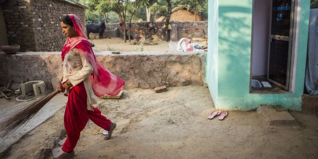 A resident walks away after cleaning a toilet block, recently built by villagers with support from Sulabh...