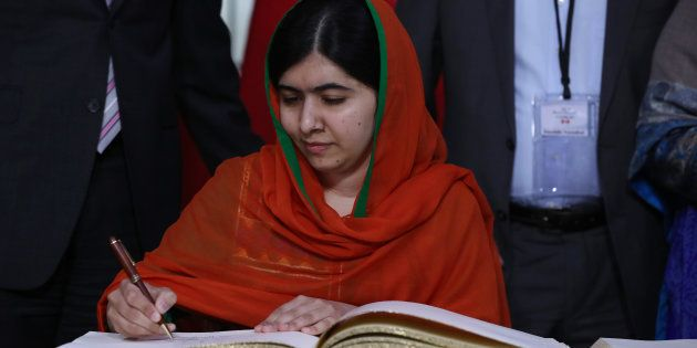 Malala Yousafzai signs a guest book at Parliament Hill in