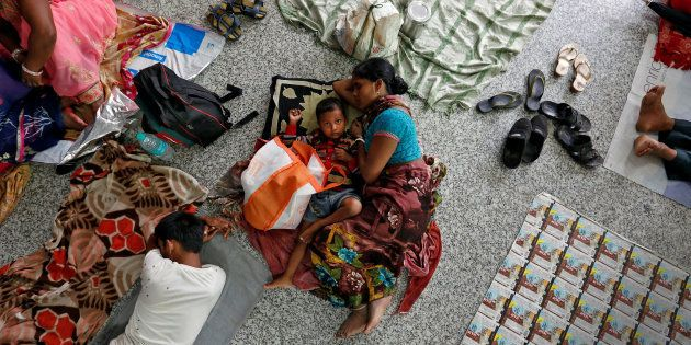 People rest on the floor outside the intensive care unit (ICU) of the Baba Raghav Das hospital in the...