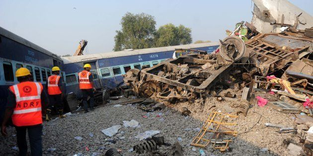 Indian rescue workers search for survivors in the wreckage of a train that derailed near