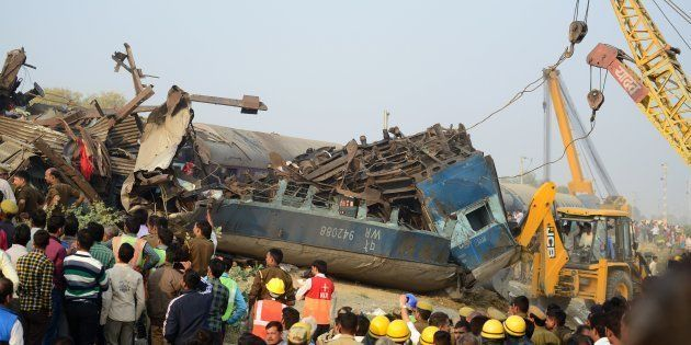 Rescue workers search for survivors in the wreckage of a train that derailed near Pukhrayan in Kanpur...