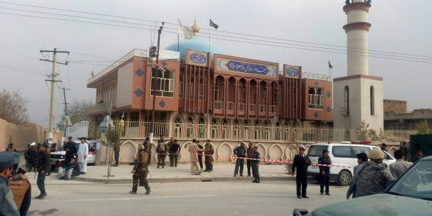 Afghan security forces keep watch in front of a mosque where an explosion happened in Kabul, Afghanistan...