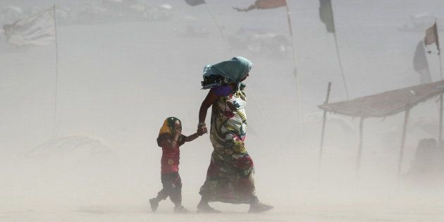 FILE PHOTO: A girl covers her eyes as she walks with her mother on the banks of the Ganges river during...