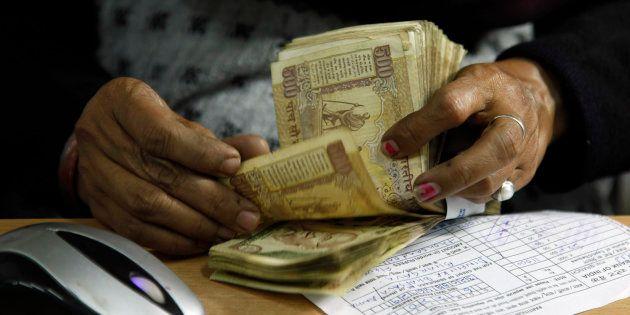 A cashier counts bank notes at a bank in Allahabad, India. (AP Photo/Rajesh Kumar Singh,
