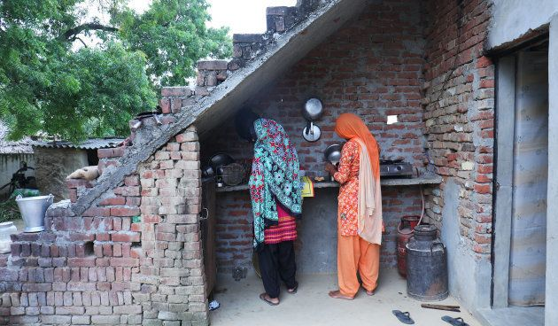 Manvi's mother (R) makes tea at their home in Dhanauri Mafi village in