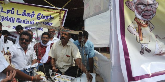 Members of trade unions set up a mock waste-paper sale counter for the exchange of 500 and 1000 rupee...