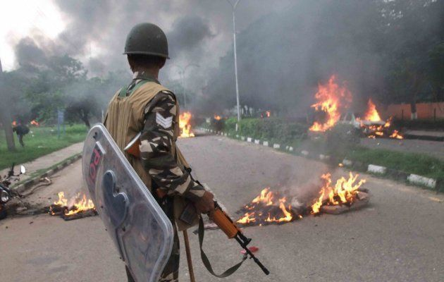 Panchkula: A Security personnel stands towards vehicles burning in violence following Dera Sacha Sauda...